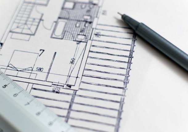 Eine richtige private Bauberatung beinhaltet das Anfertigen und Strukturieren von Bauzeichnungen und Archtiktenplänen. Auf dem Bild ist ein Architektenplan sowie ein Bleistift zusehen.