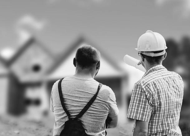 Auf dem Bild sind zwei Männer dargestellt, die von hinten zu sehen sind, wobei ein Mann einen Helm trägt und seinem Kunden den Bauprozess erklärt.